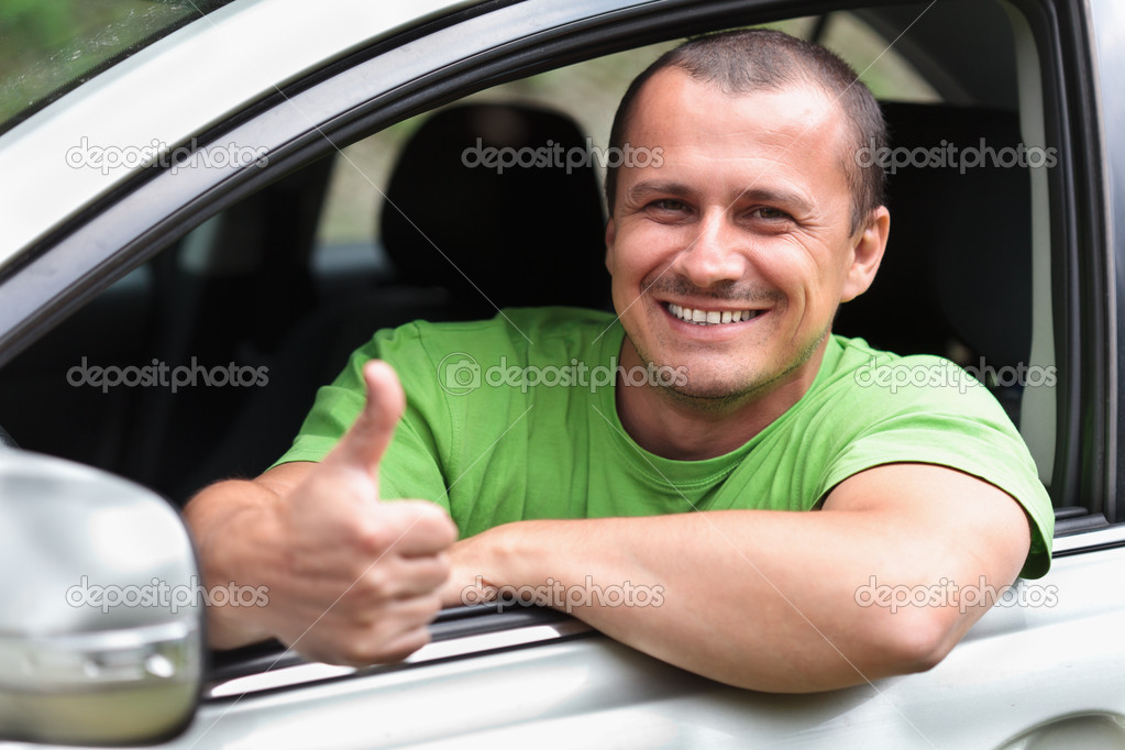 Happy young caucasian man at the wheel of his new car — Stockfoto #5903477