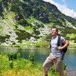 Mountaineer with backpack hiking into mountains — Stock Photo #5960302