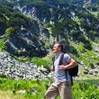 Mountaineer with backpack hiking into the mountains — Stok fotoğraf
