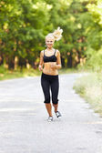 Young blond woman running — Stock Photo