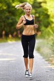 Joven mujer rubia corriendo — Foto de Stock