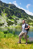 Mountaineer with backpack hiking into the mountains — Stock Photo