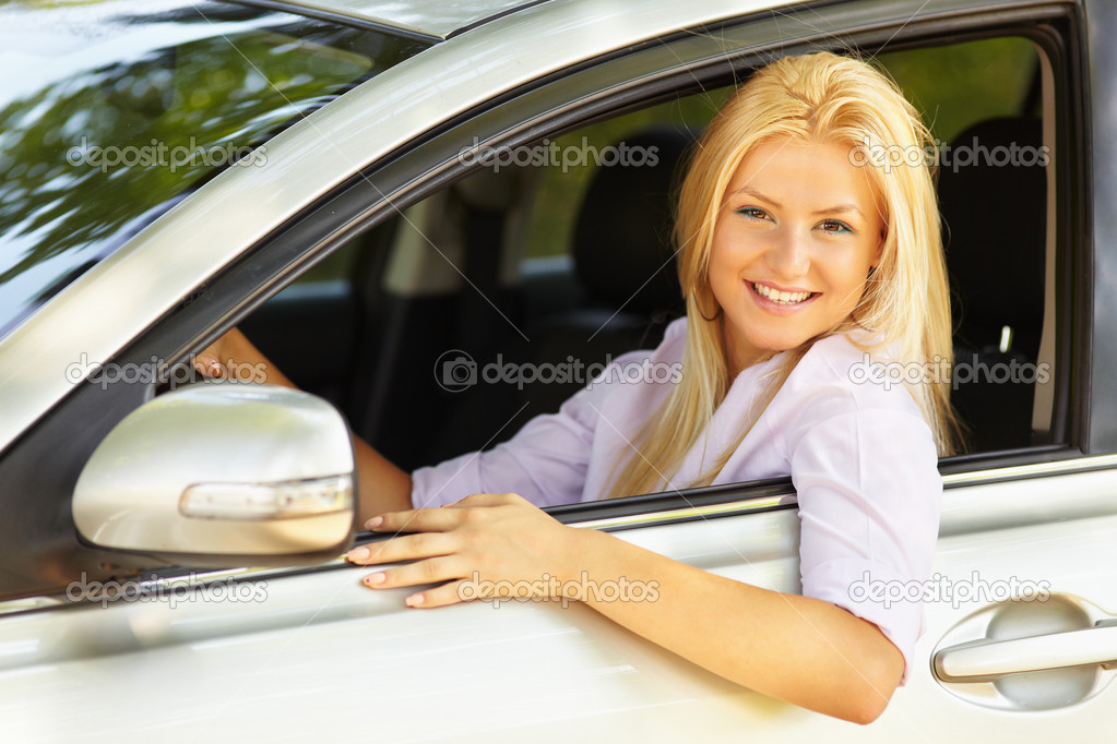 Attractive blonde young woman at the wheel in her new car — Photo #5960235
