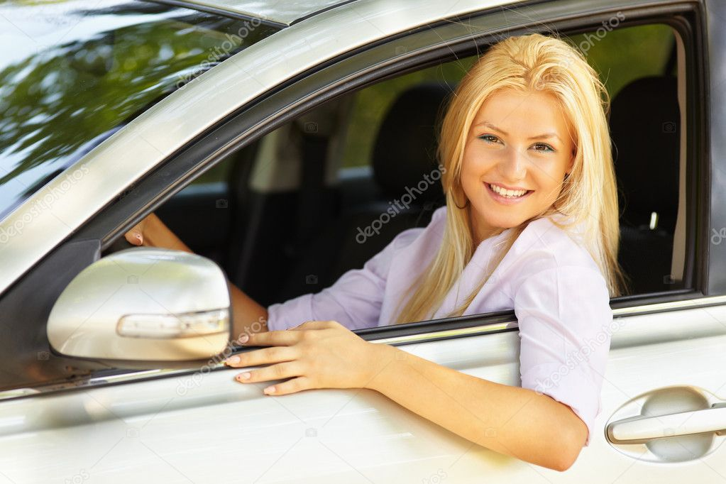 Attractive blonde young woman at the wheel in her new car — Foto Stock #5960235