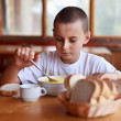 Child eating soup in a restaurant — Стоковое фото