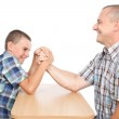 Father and son having fun with arm wrestling — Stock Photo