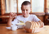 Child eating soup in a restaurant — Stock Photo