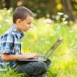 Boy using laptop outdoor — Stock Photo