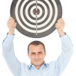Businessman holding target above his head - Stock Photo