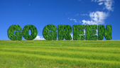 Go Green sign over fresh grass — Stock Photo
