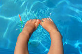 Legs of a child into the water — Stock Photo