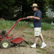 Man using a garden tiller — 图库照片