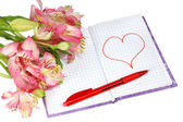 Notebook with a pen by flowers and heart — Stock Photo