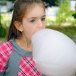 Girl eating sweet cotton wool — Stock Photo