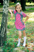 Flickan står nära träd — Stockfoto