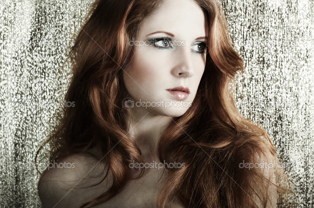 Fashion portrait of a young beautiful redheaded woman on a gold background — Stock Photo #5389071