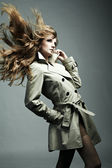 Fashion portrait of young beautiful woman in the raincoat — Stock Photo