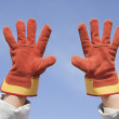 Stock Photo: Two working gloves against blue sky