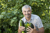 Satisfied man with three zucchin — Stock Photo