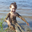 Baby girl in mud on river — Stock Photo #6271041