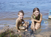 Children in the mud on the river — Stock Photo
