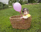 Baby girl in the basket with the ball — Stock Photo
