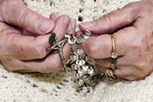 Hands holding rosary — Stock Photo