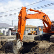Orange digger and deep hole — Stock Photo