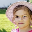 Smiling little girl with straw sunhat — Stock Photo