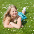 Teenager girl lying on grass - Stock Photo