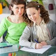 Girl doing homework with her mom — Stock fotografie