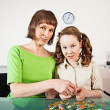 Teenager girl assembling jigsaw with her mother — Stock Photo #5908987