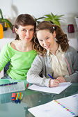 Girl doing homework with her mom — Foto de Stock