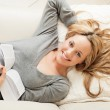 Stock Photo: Happy young woman lying with book