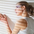 Woman standing by the window with blinds — Stock Photo