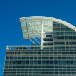 Modern Blue Glass Office Tower with Curved White Roof Under Sky — Stock Photo