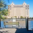 Royalty-Free Stock Photo: Huge Hotel Across River From Empty Bench