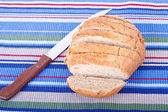 Fresh Whole Grain Bread Sliced on Placemat with Knife — Stock Photo