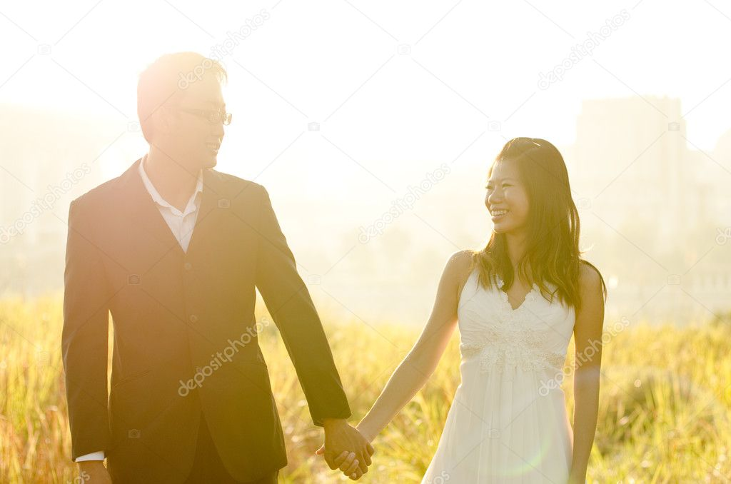 Bride and Groom holding hands, surrounding by natural morning golden sunlight. — Stock Photo #5910487