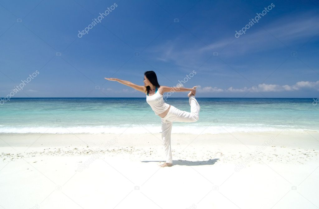 Woman practising Yoga (Warrior Position) on the beach. — Stock Photo #5910628