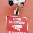 Security / surveillance camera with the warning sign - Stock Photo