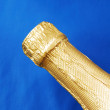 Close up view of a champagne bottle isolated on blue - Stock Photo