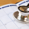 A stethoscope on the calendar concepts of medical appointment — Stock Photo