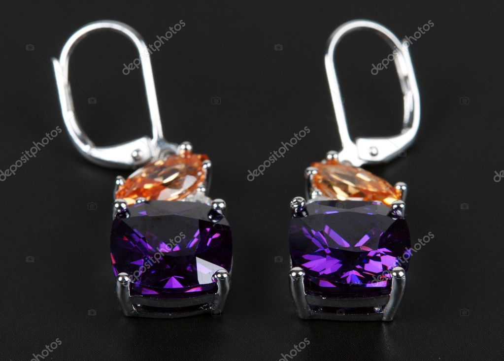 Earrings with purple stones on a black background — Stock Photo #5511898