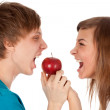 Boy and a girl biting the apple — Stock Photo
