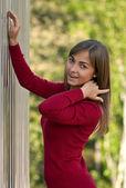 Beautiful girl in purple dress outside steel wall — Stock Photo