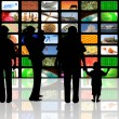 Young with children watching television on huge lcd panel — Stock Photo