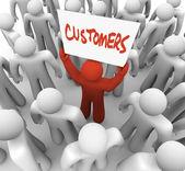 Person som innehar kunder tecken i skara — Stockfoto