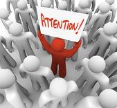 Pessoa que detém o sinal de atenção em multidão para ser reconhecido — Foto Stock