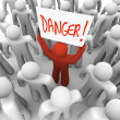 Danger - Person Holding Sign to Warn or Alert Others - Stock Photo